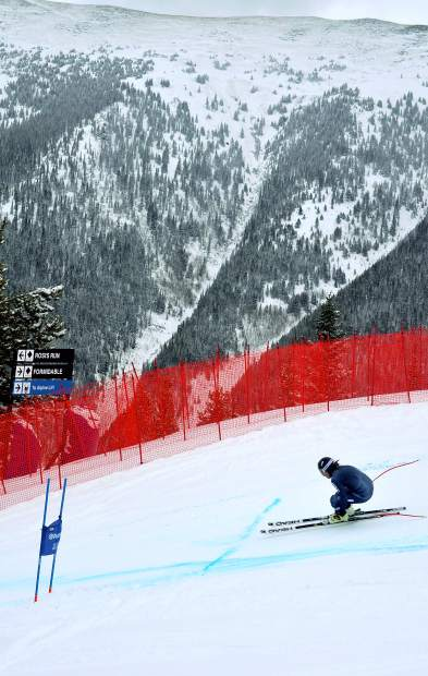 An unidentified national team skier tucks low for a gate on the early-season downhill course at Copper Mountain on Nov. 19.