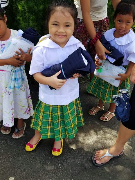 A young resident of Tacloban, Philippines, shows off the school uniform and supplies she received from Aspen residents John ODonoghue and Tony Bell, who recently visited the islands to help the 2,000 children living there in poverty.
