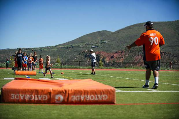 Broncos' player Kyle Peko directs a little girl through a football drill Saturday morning at Aspen High for a kids' camp.