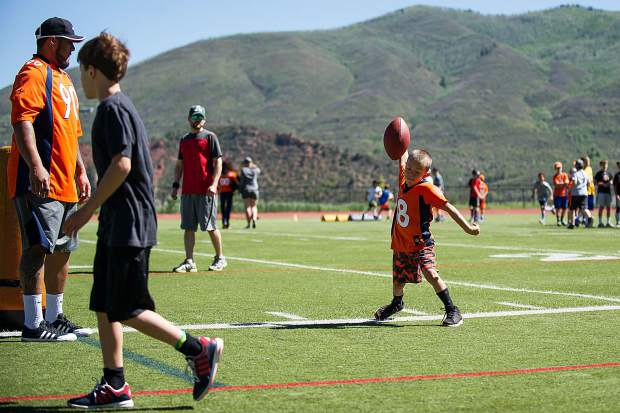 A little boy spikes the football at a Broncos' camp held at Aspen High School Saturday morning.
