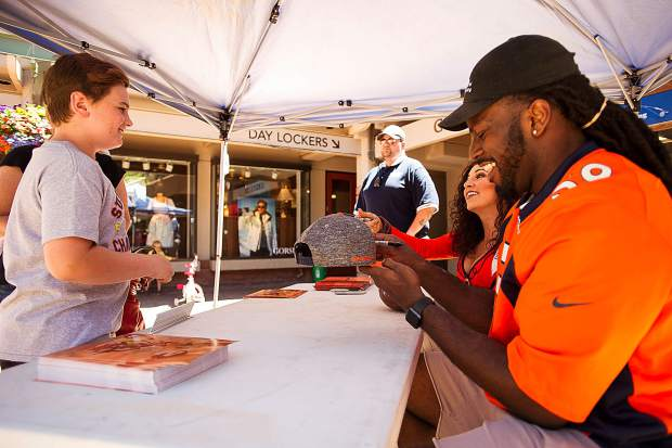 Broncos player Vontarrius Dora and Broncos' cheerleader Gioia Bartalo signing an autograph for Ethan Birmingham, 10, Saturday in the gondola plaza in Aspen.
