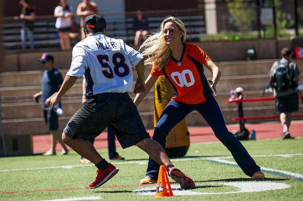 Broncos' cheerleader Hayley McDonald blocks during a drill at the Broncos' football camp held at Aspen High School on Saturday.