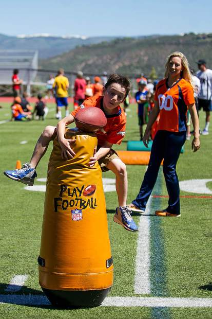 Tharyn Mulberry, 8, leaps into a tackle drill held on Aspen High School's football field by Broncos players on Saturday.
