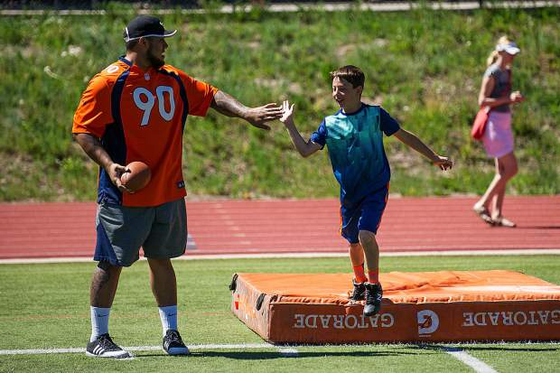 Brett Eggleston, 9, gives Broncos' player Kyle Peko a high five after completing a drill during a camp held at Aspen High School's football field on Saturday.