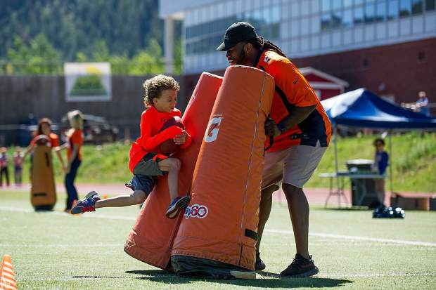 Max Rooding, 7, leaps into one of the drills that Bronco's player Vontarrius Dora is holding on Aspen High School's football field Saturday morning.