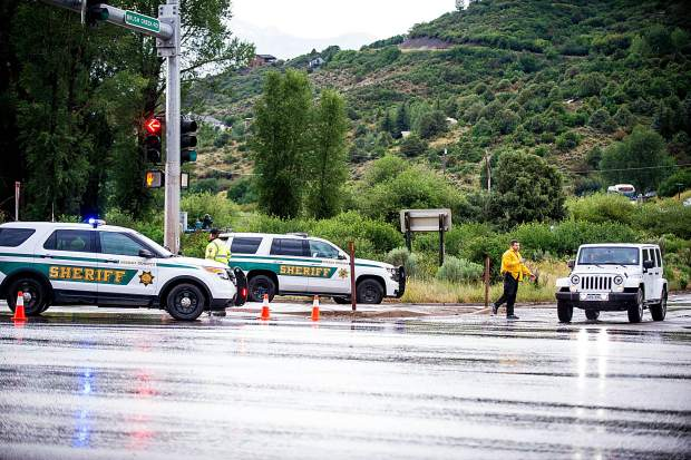 Pitkin County deputies divert eastbound traffic up Owl Creek Road on Tuesday due to a series of rockslides caused by heavy thunderstorms that closed Highway 82 near the Aspen Airport.