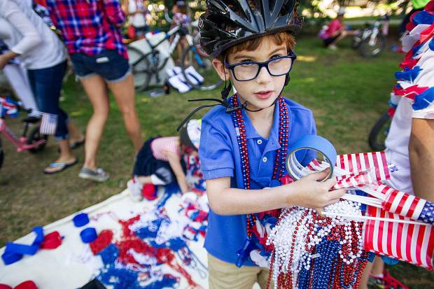 A little boy gathers decorations for his bike before the parade in Aspen on Tuesday at Paepcke Park.