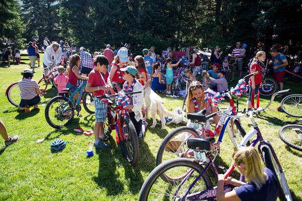 Children prep their bikes for the Aspen parade Tuesday morning in Paepcke Park.