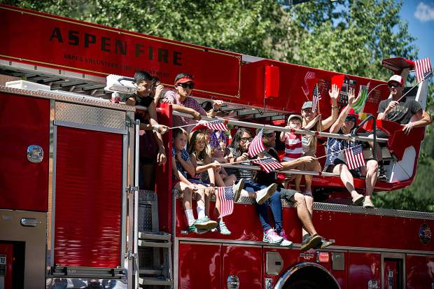 Children on the Aspen Firetruck float in the Aspen parade on Tuesday.