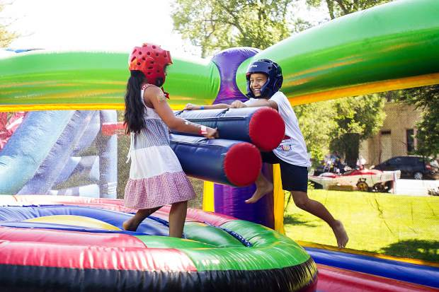 Taylor Taylor, 7, left, knocks down Jackson Braddock, 9, in the bounce house at Paepcke Park on Tuesday.