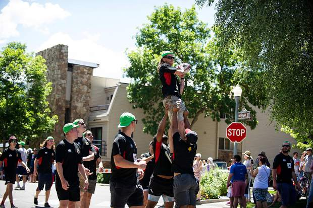 The Gentlemen of Aspen rugby players make a catch during the parade on Tuesday.