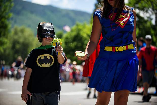 A little boy dressed as Batman blows bubbles in the parade on Tuesday.