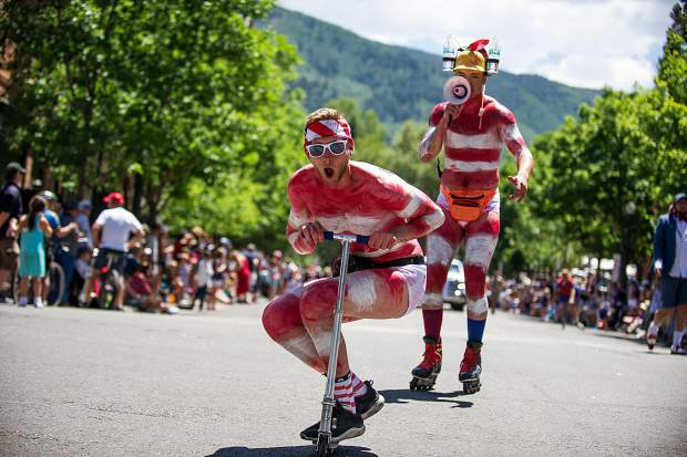 Boomer Bate rides his scooter in the parade with friend Jordan Reitsma behind him in Aspen on Tuesday.