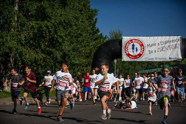 A group of boys lead the pack for the family and canine Boogie's Buddy Program run in Aspen on Tuesday.