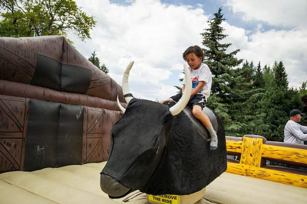 Lucca Bevilacqua, 7, rides the bull at the AVSC picnic in Aspen on Tuesday.