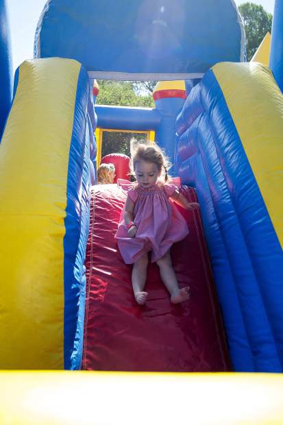 Olivia Walters, 2, slides down a bouncy house slide in Paepcke Park on Tuesday.