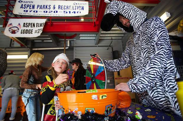 Spencer Irvin, 8, picks out a piece of candy at the Aspen volunteer fire department on Tuesday for their Ellks Lodge Hallooween