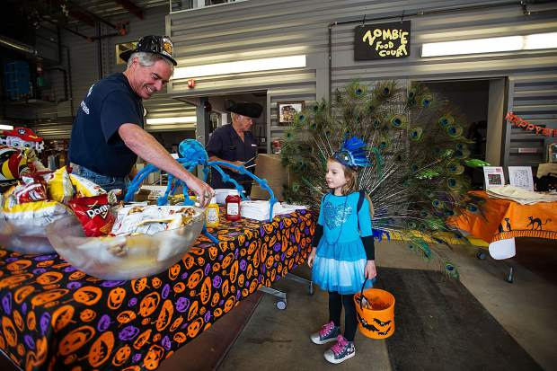 Zsofia Bartha, 4, receives snacks from firefighter Scott Arthur Tuesday at the Aspen Fire Department event sponsored by the Elks Lodge for Halloween.