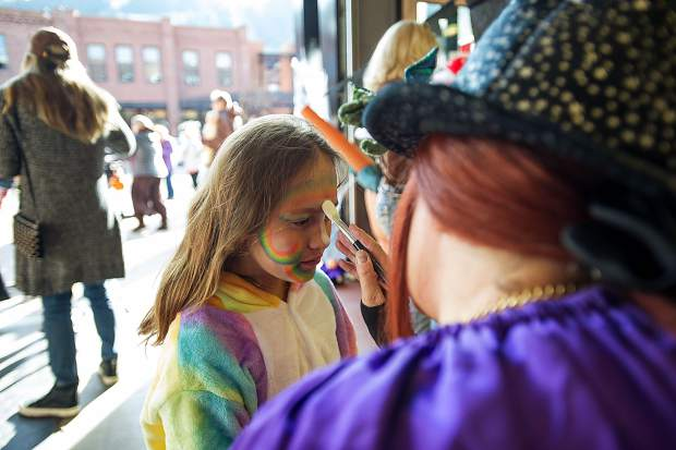 A little girl gets her face painted at the