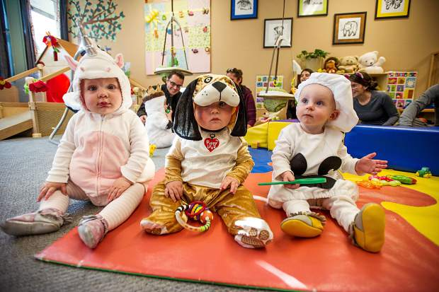From left to right, Charlotte Janien, 1, Briggs Myatt, 8 months, and Amelia Szoradi, 11.5 months, enjoy a party at the Yellowbrick daycare center on Tuesday for Halloween.