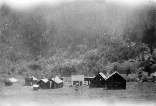 One b/w photograph showing the town of Ashcroft in 1920. Several buildings are visible, and the one with white paint is the Blue Mirror Saloon and the one across from it with a facade is the old Post Office.