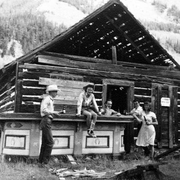 One b/w photograph of the the Blue Mirror Saloon in Ashcroft. A wooden bar sits outside and five people are surrounding it (left to right-unidentified man, Joan Trumbull, unidentified man, unidentified man, and Maud Banks). Joan is sitting on the bar and has a splint on her left leg, and all of them are drinking a beer. The saloon is falling apart, and there is wood scattered around on the ground. 1948