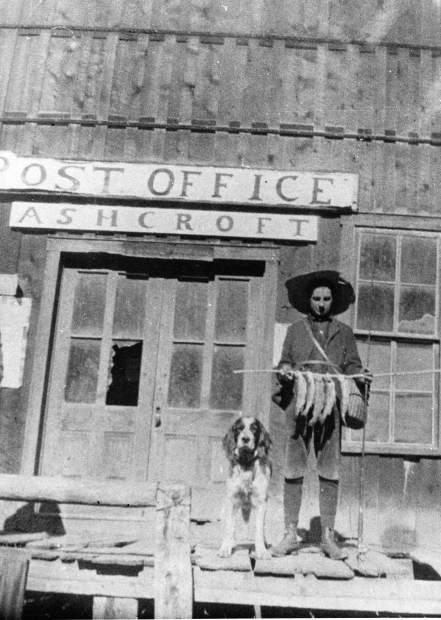 One b/w glossy photograph of the old Post Office in Ashcroft. A young person holding a catch of fish is standing on the old wooden porch. There is a dog standing next to him. 1900-