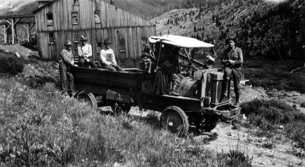 One b/w photograph of several men in a World War One army truck with solid rubber tires, 1920-. The photo was taken along Independence Pass, near the ghost town. The mill can be seen in the background.