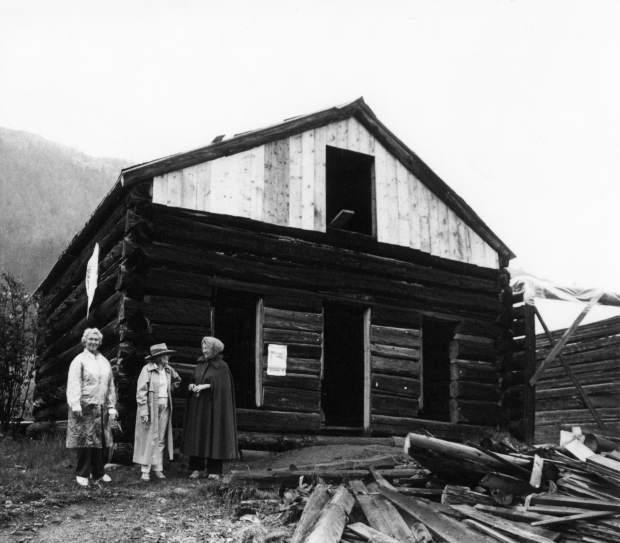 One b/w photograph of three unidentified women standing in front a building at the ghost town of Independence. The building is being restored, and the upper section of the building is constructed of new, lighter wood, and there are several pieces of dark wood lying in front of the building. The women were at Independence to celebrate the
