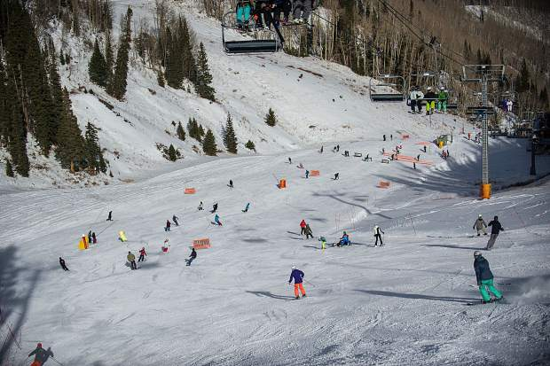 Skiers and snowboarders make their way down Aspen Mountain on opening day on Thursday.