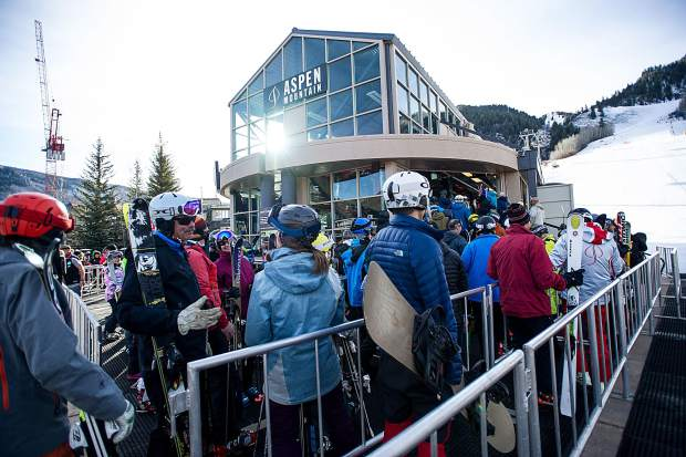 Skiers and snowboarders filter through the lines at the Silver Queen Gondola on opening day at Aspen Mountain on Thursday.