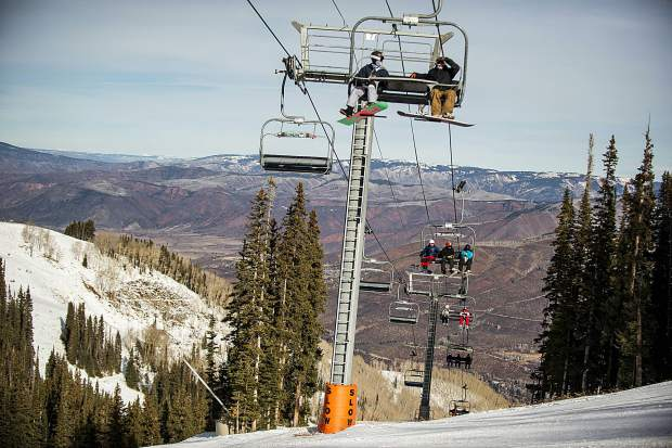 Skiers and snowboarders ride up the Ajax Express on Aspen Mountain for opening day Thursday.