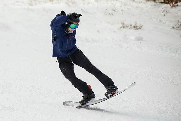 A snowboarder does a 180 on the Little Nell run on Aspen Mountain for opening day Thursday.
