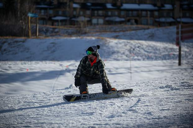 A snowboarder gets low coming down Fanny Hill in Snowmass for their opening day on Thursday.
