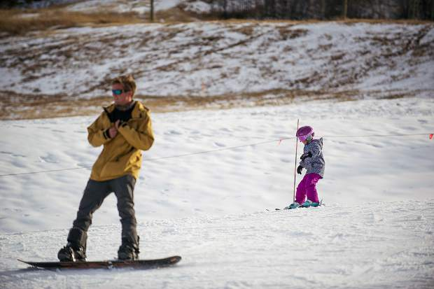 A skier and a snowboarder make their way down Fanny Hill Thursday afternoon of Snowmass Mountain's opening day in November 2017.