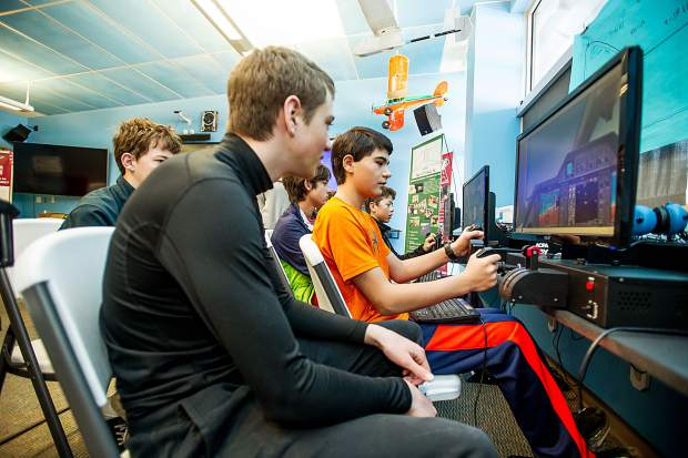 8th grade students in Keri Benton's aviation class at Aspen Middle School working on the flight simulators in their classroom on Thursday. Zane Zachary piloting the simulator.