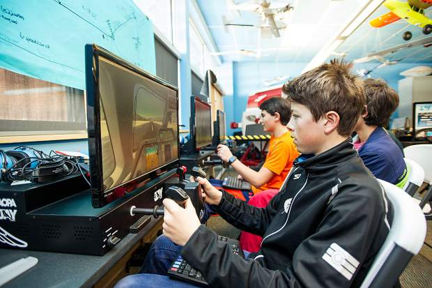 8th grade students in Keri Benton's aviation class at Aspen Middle School working on the flight simulators in their classroom on Thursday. Anders Weiss piloting the simulator.