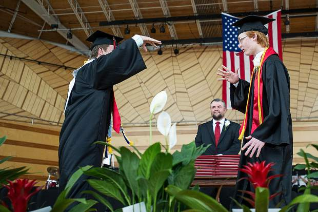 Two seniors do a fun handshake on stage at the beginning of the Aspen High School graduation ceremony on Saturday at the Benedict Music Tent.