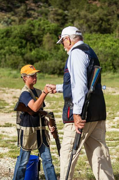 U.S. Navy Veteran Bob Perigo fist bumps one of the students he coaches with 4H Hunter Oger, 12, at the Basalt shooting range on Wednesday evening. Perigo credits focusing on his shooting skills for cleaning up his lifestyle.