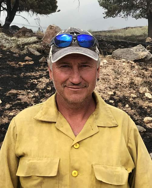 Firefighter Cleve Williams on July 5 on Vista Hi Drive, where the Lake Christine Fire destroyed his house.