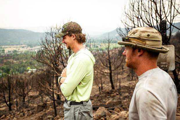 Indy Lane, left, and Cory Ross, standing on the edge of the Lane family's property in El Jebel that was destroyed by the Lake Christine Fire. The Lane family also encountered flash flooding from Saturday's storms creating mudslides on their property.