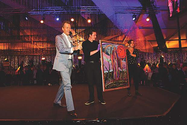 Auctioneer Oliver Barker, Chairman of Sotheby's Europe, presents lot 6, Talk to the Moon by artist Josh Smith. MarySue Bonetti photo.