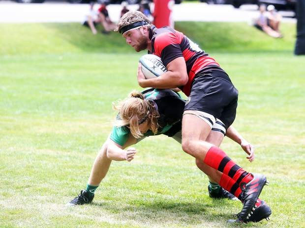 Aspen rugby player James Kistner attempts to run through a Grand Junction player during a match on Saturday, Aug. 4, 2018, at Wagner Park in Aspen. (Photo by Austin Colbert/The Aspen Times).