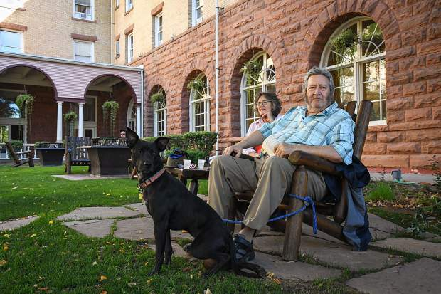 Glenwood Springs residents Victoria and Eddy Monge sit in the Hotel Colorado courtyard with their dog Jemma during the Big BIrthday Bash on Saturday morning.