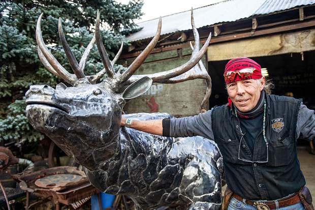 El Jebel Blacksmith Vaughn Shafer poses Wednesday with the bull elk he recently finished. Shafer and sculptor Thomas Barlow were commissioned to create three handcrafted, metal elk for the El Jebel roundabout.