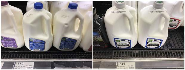 In this Thursday, Jan. 17, 2019, combination photo, regular 2 percent fat milk, left, is shown for sale at $3.69 per gallon, and organic 2 percent fat milk is shown for sale at $7.49 per gallon, at a grocery store in Doral, Fla. U.S. shoppers are still paying more for organic food, but the price premium is falling as organic options multiply.
