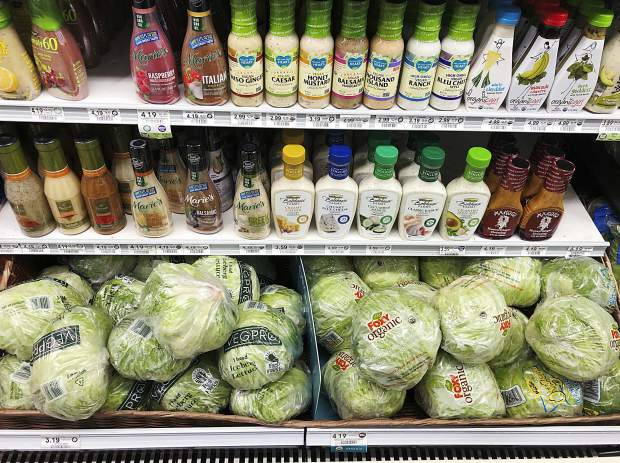 In this Monday, Jan. 21, 2019, photo, regular iceberg lettuce, lower left, selling at $3.19 each, is displayed next to organic iceberg lettuce selling at $4.19 each, at a grocery store in North Miami, Fla. U.S. shoppers are still paying more for organic food, but the price premium is falling as organic options multiply.