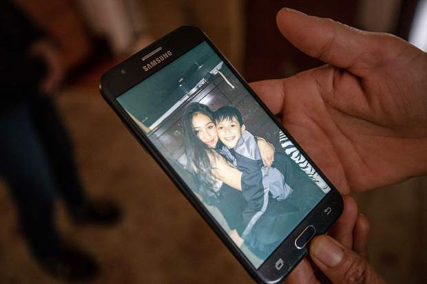 Estela Garcia Lopez shows a picture she has of her two children on her cell phone. She said she lost most of her pictures in the fire.