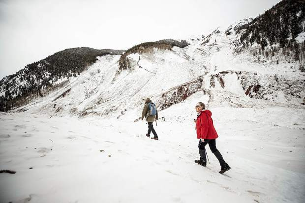 Art Mears, an avalanche expert from Gunnison, and his wife, Paula Lehr, hike Tuesday on the vast snow and debris flow left in the Condrum Creek Valley by an avalanche last weekend.