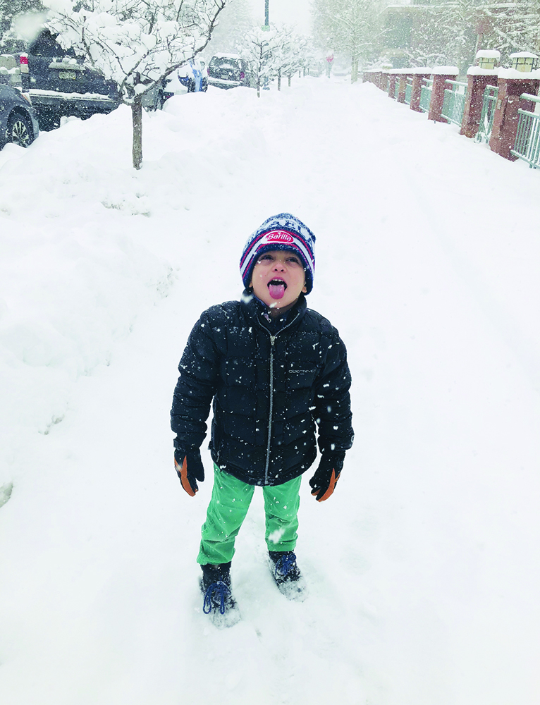 Remy Selby taste tests snowflakes on a snow day from school.